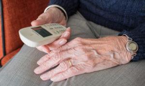 Las manos de una persona de avanzada edad sosteniendo un teléfono.