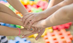 Varios niños entrelazan sus manos en una actividad colaborativa.