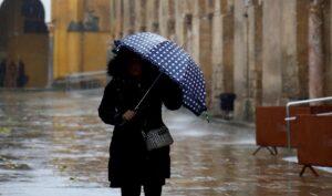 Mujer caminando por la calle bajo la lluvia.