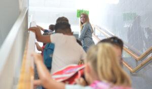 Niños de Primaria se dirigen a su aula bajo la mirada de una trabajadora del centro escolar.