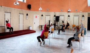 Varias personas hacen ejercicios en un Centro de Participación Activa para mayores.