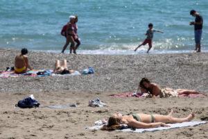 Varios bañistas al sol en una playa de Málaga (Agencia EFE).